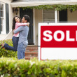 Hispanic couple outside home with sold sign — Stockfoto