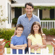 Stock Photo: Father and children outside home