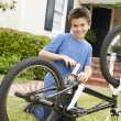 Stock Photo: Boy fixing bike in garden