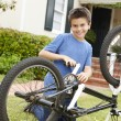 Boy fixing bike in garden - Stock Photo