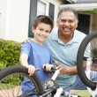 Stock Photo: Boy and grandfather fixing bike