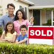 Hispanic family outside home with sold sign - Stock Photo
