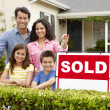 Stock Photo: Hispanic family outside home with sold sign