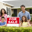Hispanic family outside home with for sale sign - Stock Photo