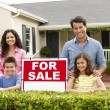 Stock Photo: Hispanic family outside home with for sale sign