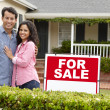 Hispanic couple outside home with for sale sign — Stock Photo