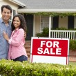 Hispanic couple outside home with for sale sign — Stockfoto