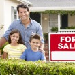 Father and children outside home for sale - Stock Photo