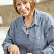 Mid age woman chopping vegetables - Stock Photo