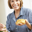 Mid age woman eating croissants — Stock Photo