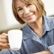 Stock Photo: Mid age womdrinking coffee