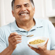 Senior man eating cereal — Stock Photo #11884622