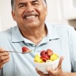 Senior man eating fruit — Stock Photo #11884624