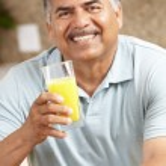 Senior man drinking orange juice — Stock Photo #11884628