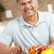 Stock Photo: Senior man chopping vegetables