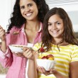 Mother and daughter eating cereal and fruit — Stockfoto