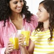 Mother and daughter drinking orange juice — Stock Photo #11884680