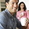 Hispanic couple relaxing in kitchen — Stock Photo #11884688