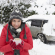 Young woman in snow with car — Stock Photo