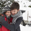 Young couple in snow with car — Stock Photo