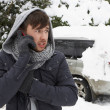 Young man in snow with broken down car - Stock Photo