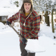 Young man clearing snow — Foto Stock