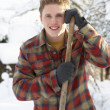 Young man clearing snow - Stock Photo