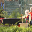 Woman working on allotment with child — Stock Photo