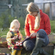 Woman and child with picnic on allotment — Stock Photo