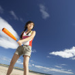 Teenage girl playing baseball on beach — Stock Photo