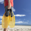 Stock Photo: Teenage boy on beach with flippers