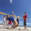 Teenagers doing limbo dance on beach — Stock Photo