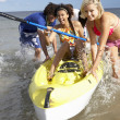 Teenagers in sea with canoe — Foto Stock