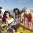 Teenagers in sea with canoe - Foto Stock