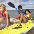 Teenagers in sea with canoe — Foto de Stock