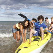 Royalty-Free Stock Photo: Teenagers in sea with canoe