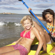 Teenage girls in sea with canoe — Stock Photo