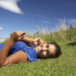 Teenage girl lying on grass with mp3 player — Foto Stock