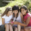 Teenage girls using phone outdoors - Stock Photo
