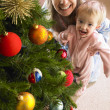 Mother and daughter with Christmas tree - Stock Photo