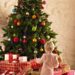 Little girl with parcels round Christmas tree - Stockfoto