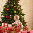 Little girl with parcels round Christmas tree - Stok fotoğraf