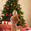 Little girl with parcels round Christmas tree — ストック写真