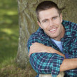 Man sitting against tree trunk - Stock Photo