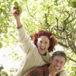 Couple picking apples off tree — Stock Photo