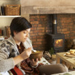 Young woman having tea by fire — Stock Photo