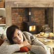 Young woman relaxing by fire — Stock Photo