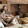 Foto Stock: Young couple relaxing by fire