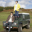 Stock Photo: Young couple in countryside with SUV