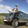 Young man in countryside with SUV - Stock Photo